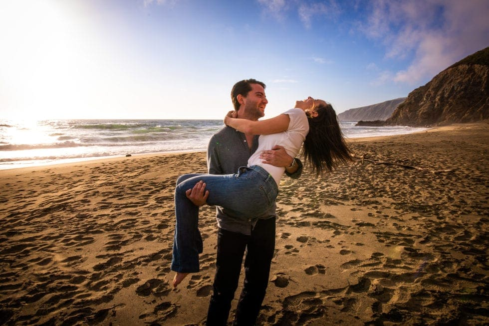man holding fiance while they laugh at point reyes seashore