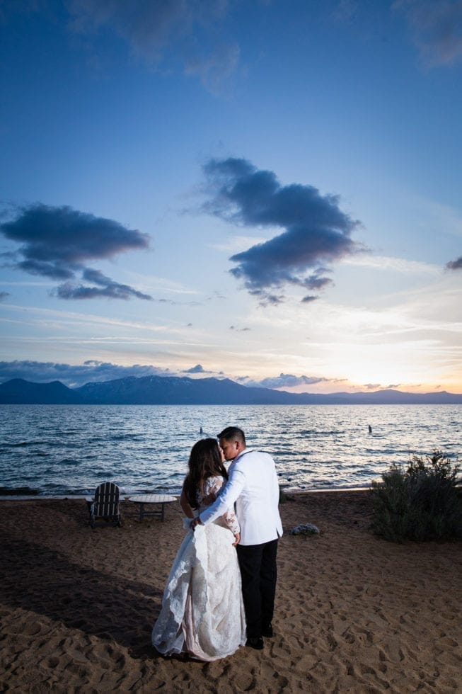 bride and groom kissing on sand in front of lake tahoe at sunset