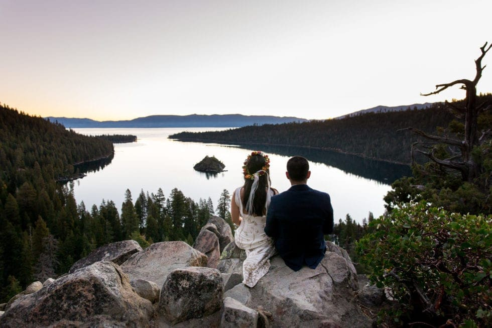 bride and groom sitting on rock and overlooking emerald bay