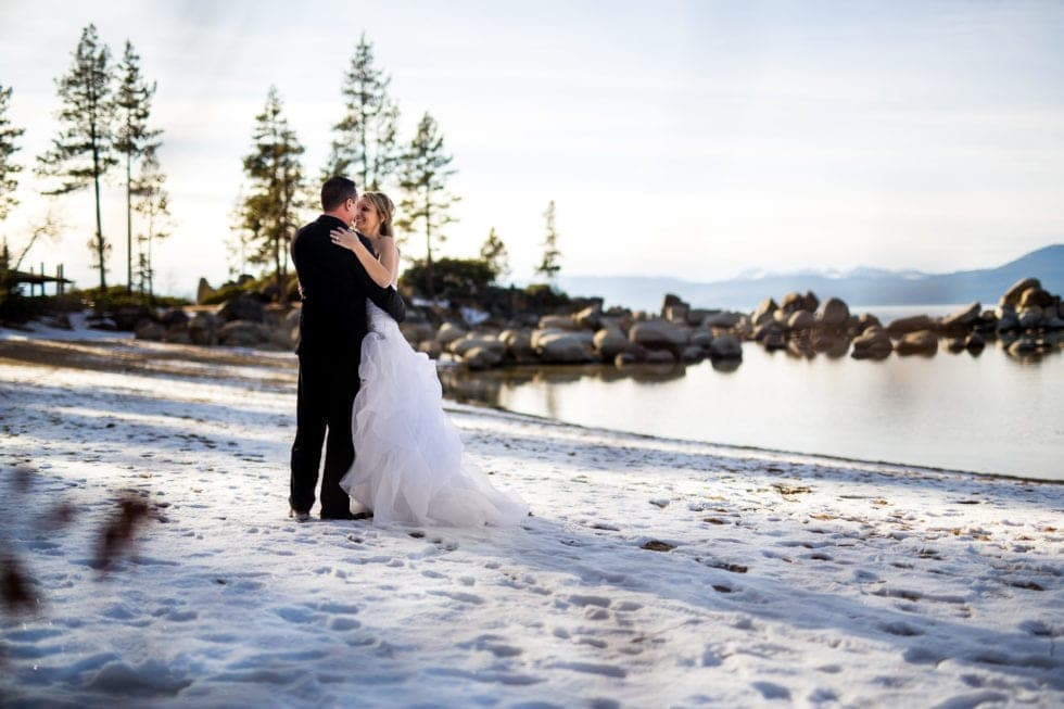 bride and groom embracing in the snow next to lake tahoe
