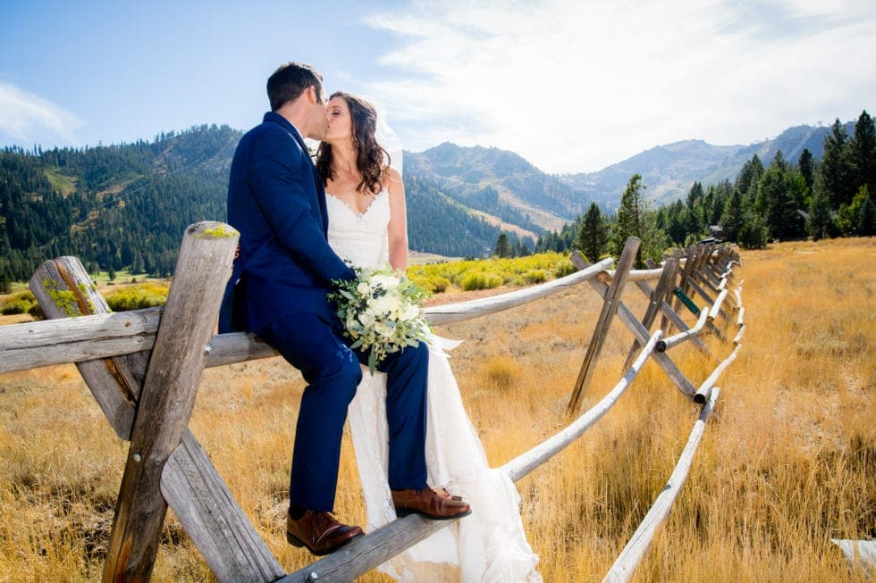 bride and groom kissing on fence at plumpjack squaw valley