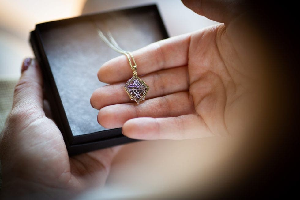 bride holding necklace received on wedding day
