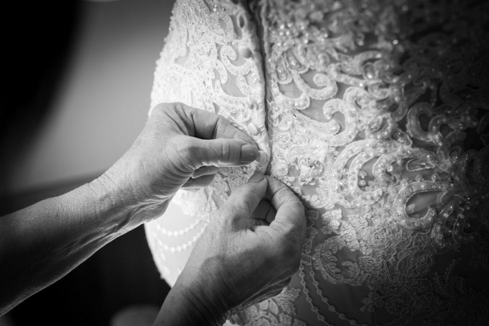 bride's dress being buttoned