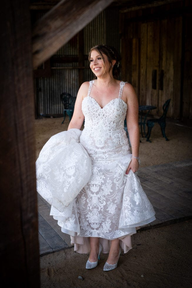 bride holding the bottom of her dress and smiling