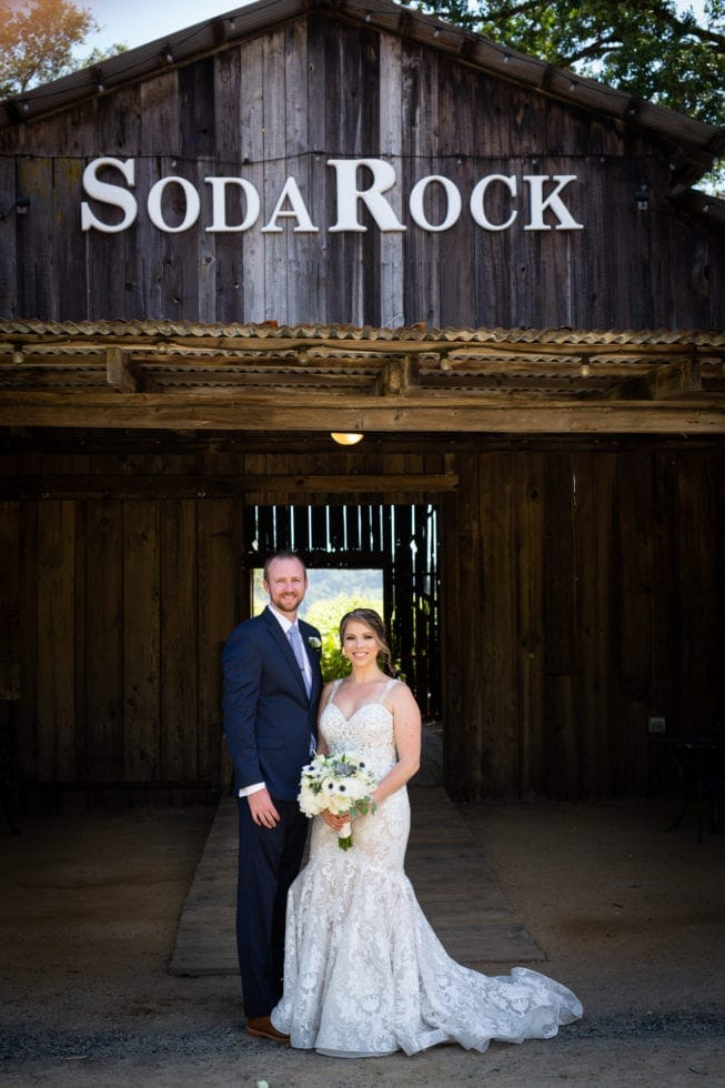 bride and groom stand in front of barn at soda rock winery