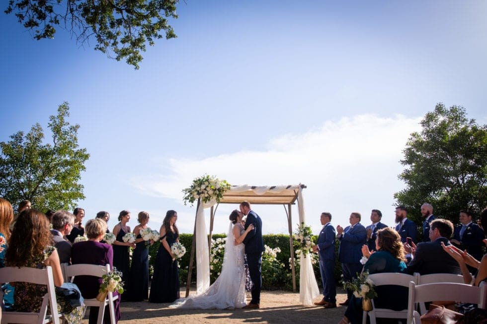 bride and groom kiss during wedding ceremony at soda rock winery