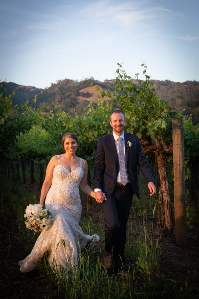 bride and groom holding hands and smiling at camera in vineyard at soda rock winery