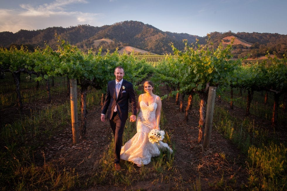 bride and groom walk toward camera holding hands with vineyard and mountain in background at soda rock winery