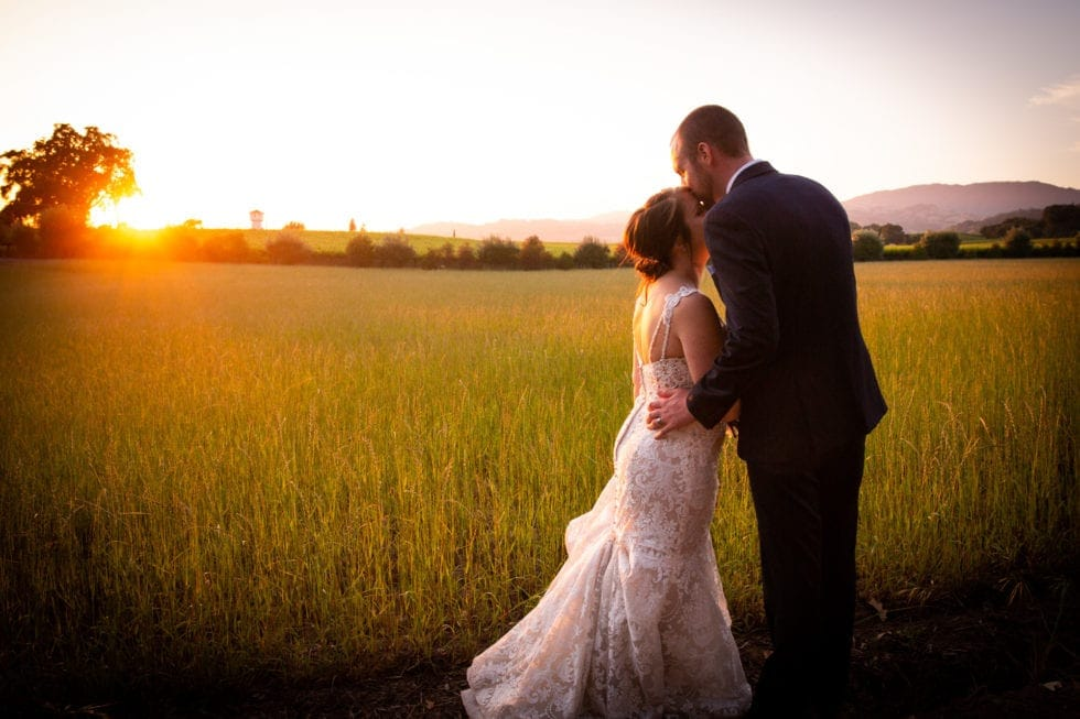 bride and groom kiss in front of field at sunset