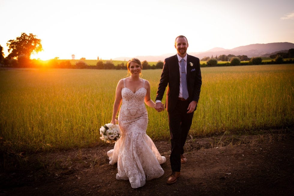 bride and groom walk toward camera in front of field at sunset