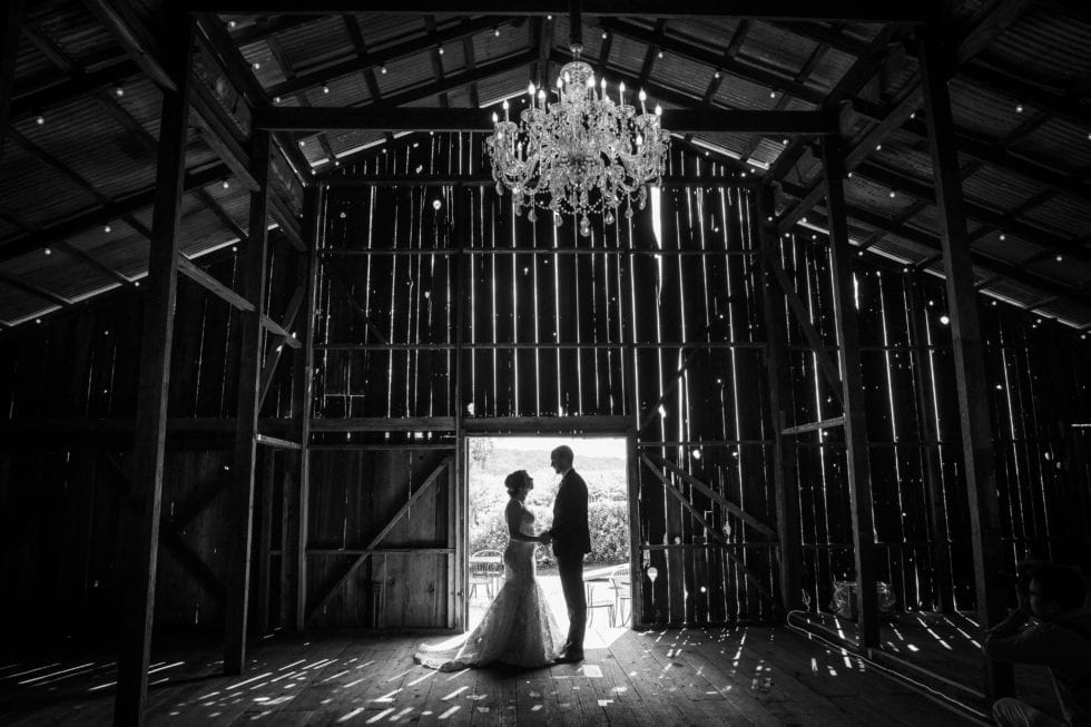 bride and groom stand in doorway of barn at soda rock winery