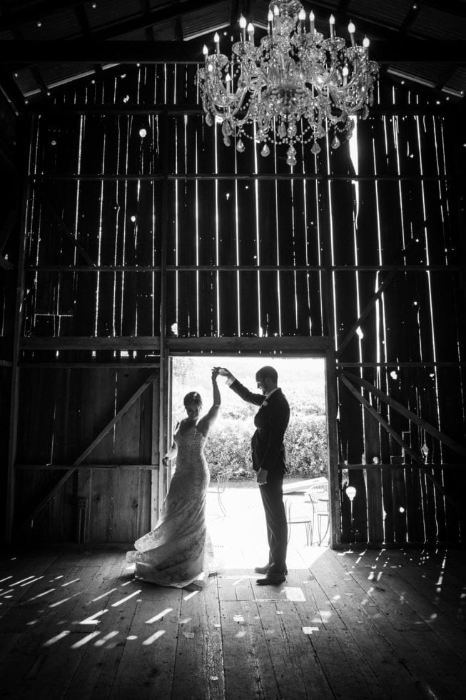 groom twirling bride in barn at soda rock winery