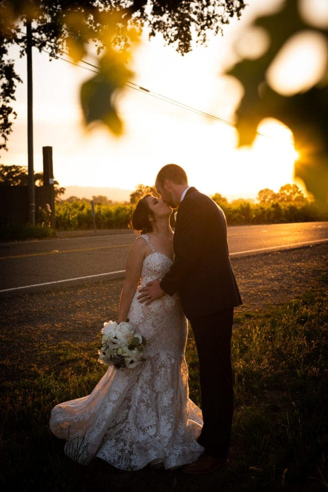 bride and groom kissing during sunset