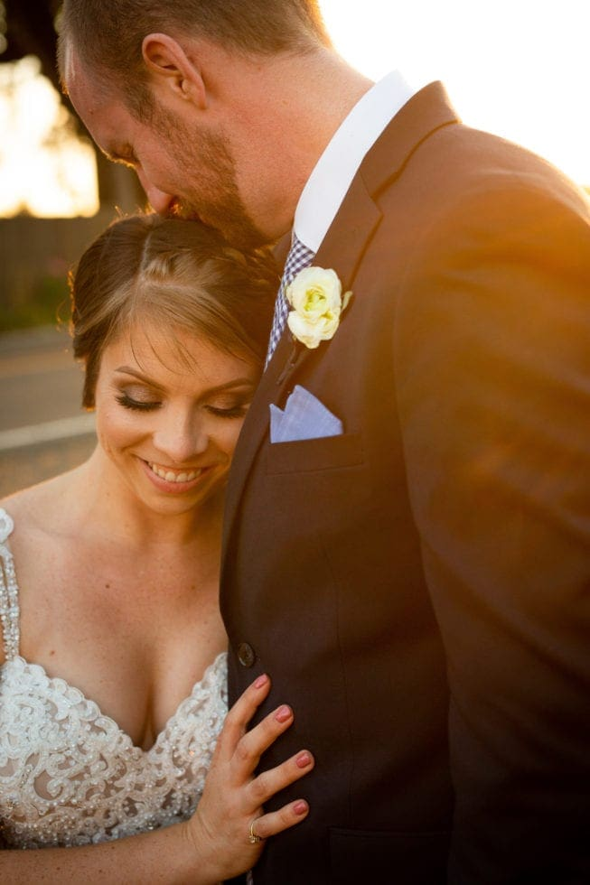 bride smiling while groom kisses her forehead