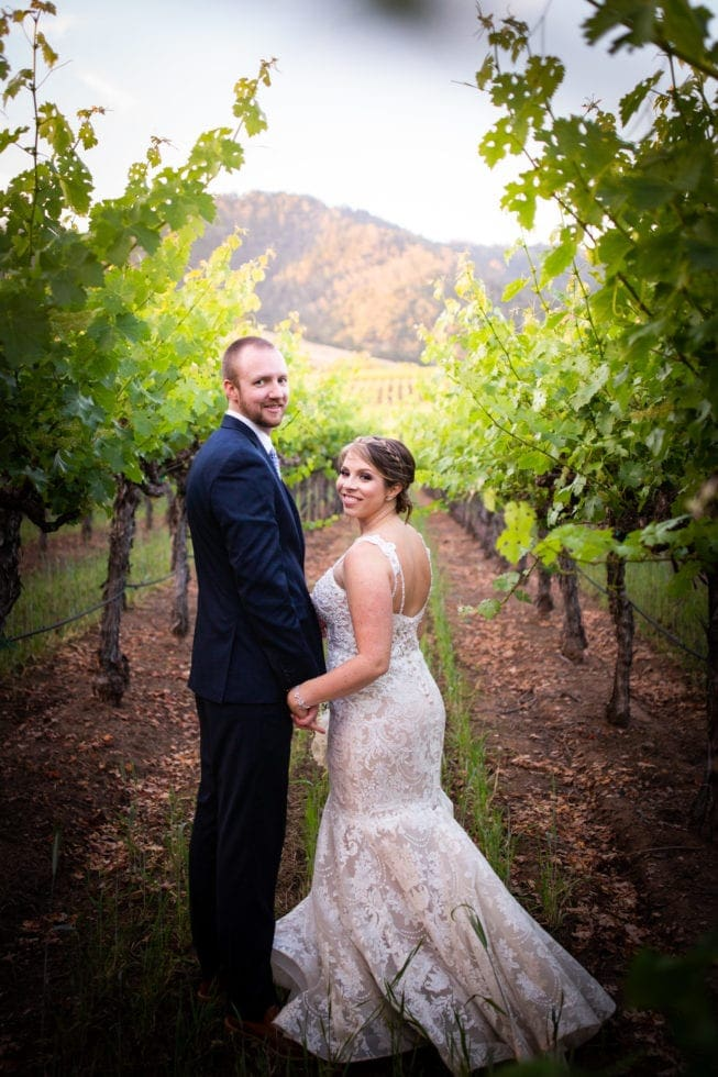 bride and groom standing in vineyard at soda rock winery