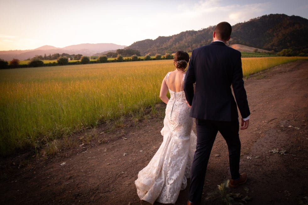 bride and groom walking on path and looking over field