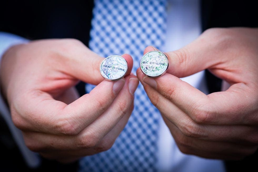 groom holding cuff links with map locations on them