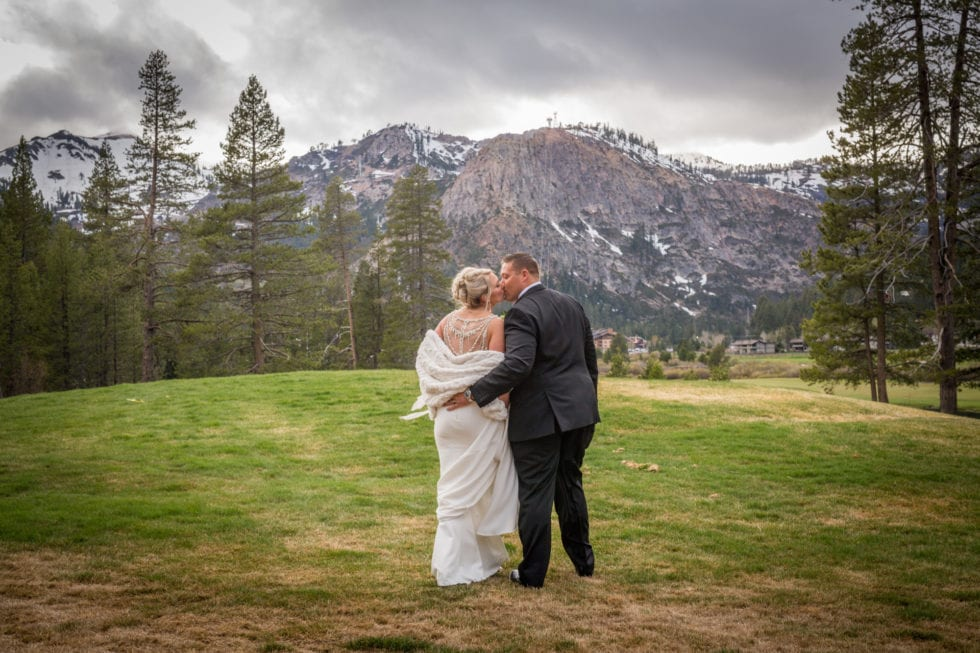 bride and groom kissing in front of mountain in squaw valley