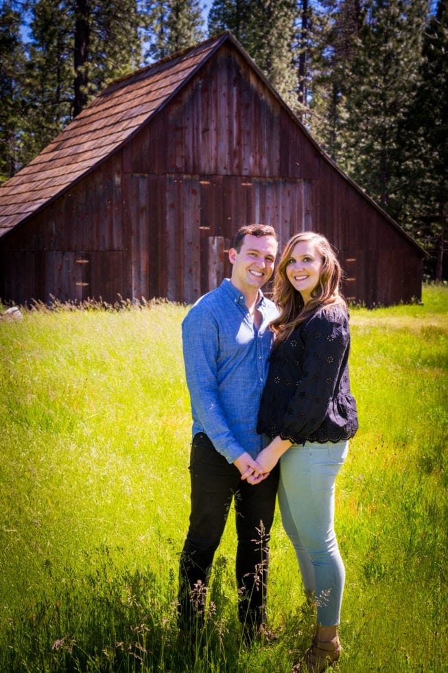 couple smiling and holding hands in front of barn in foresta ca