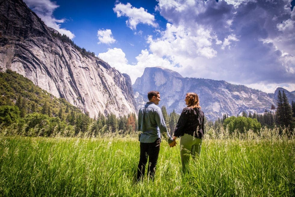 couple holding hands and looking at each other with half dome in the background