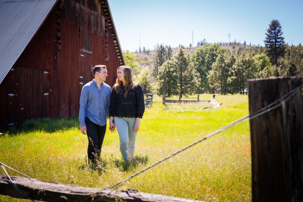engaged couple standing in front of barn at foresta ca