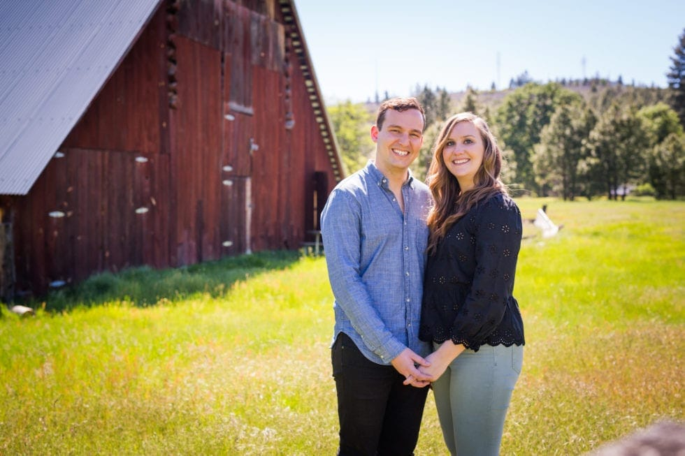 couple holding hands and smiling in front of barn in foresta ca