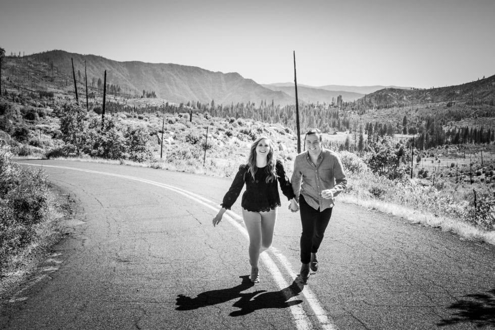 couple running on road with mountain in background during yosemite engagement session