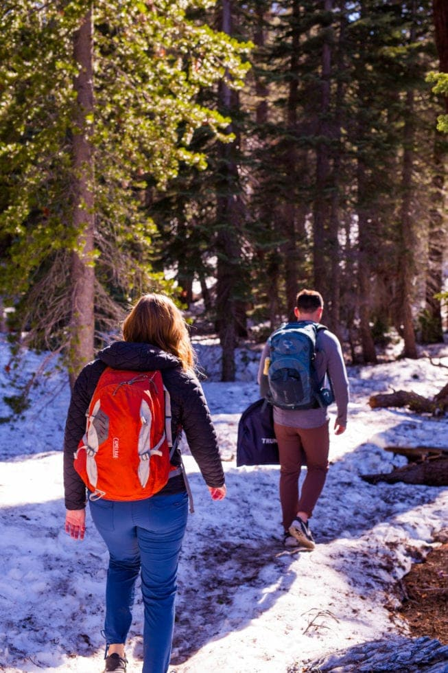 couple wearing backpacks and hiking through snow during yosemite engagement session