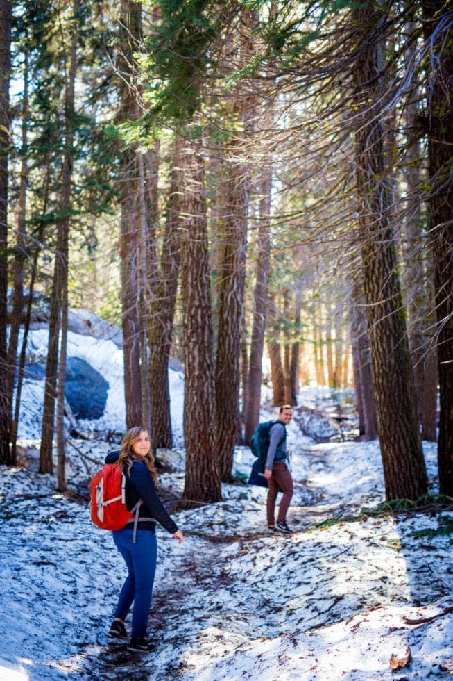 couple hiking through snow during yosemite engagement session