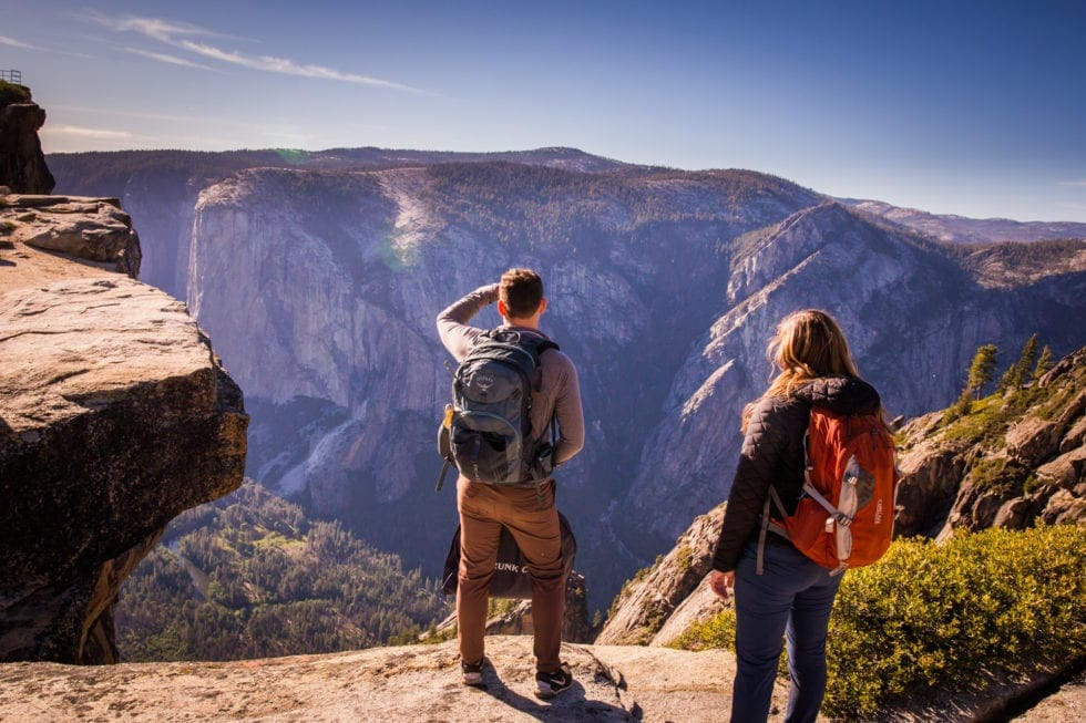 couple looking at taft point view during yosemite engagement session