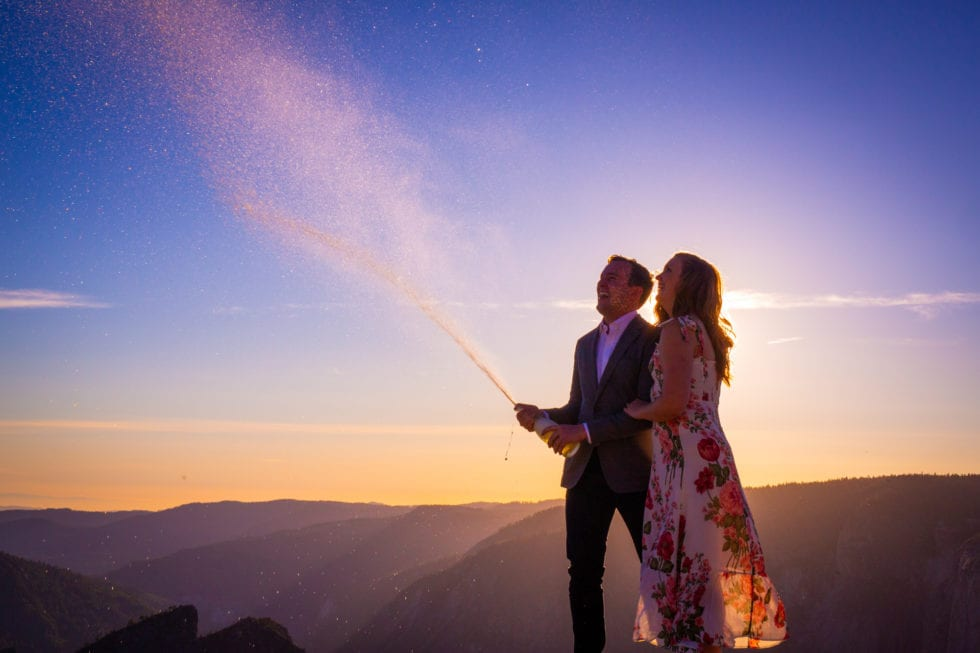 engaged couple opening champagne during yosemite engagement session