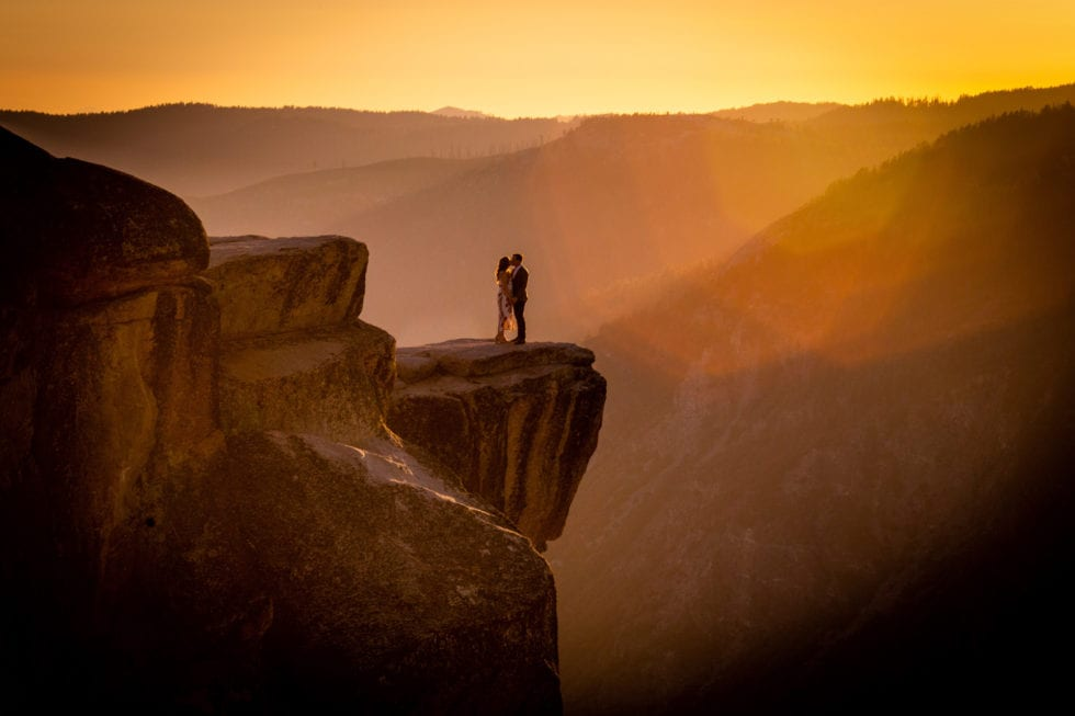 couple holding hands and kissing on ledge of taft point during yosemite engagement session