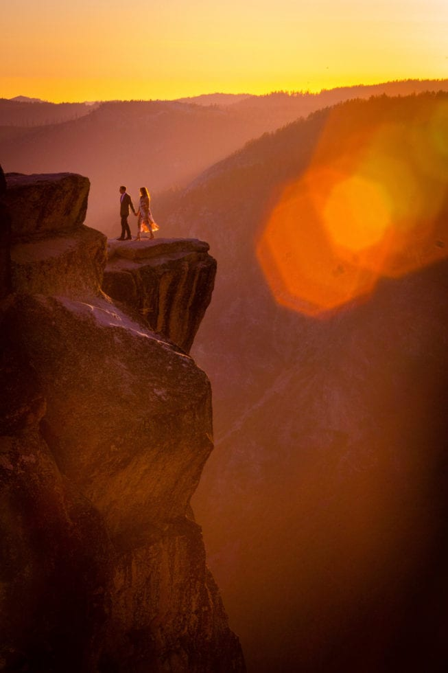 couple holding hands on taft point ledge during yosemite engagement session