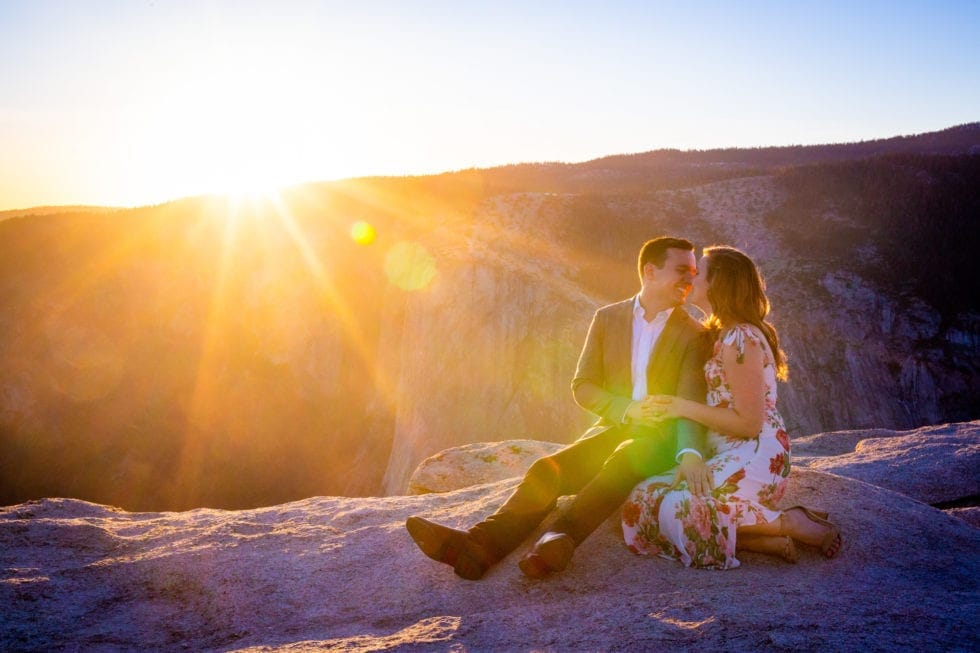 couple sitting on rocks with yosemite in the background during sunset