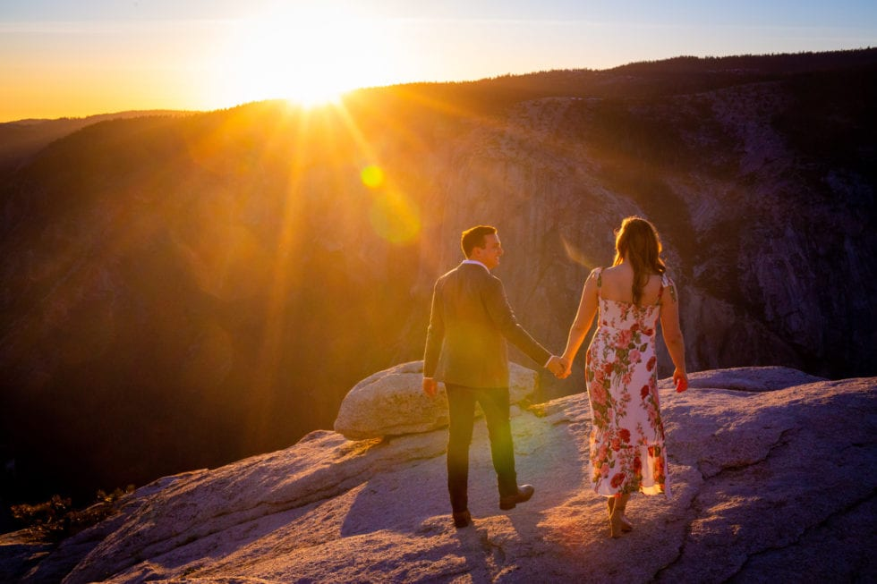 couple holding hands and walking during yosemite engagement session
