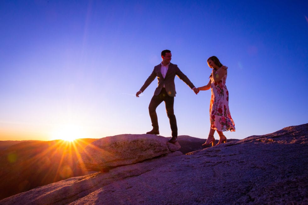 couple holding hands and walking at sunset during yosemite engagement session