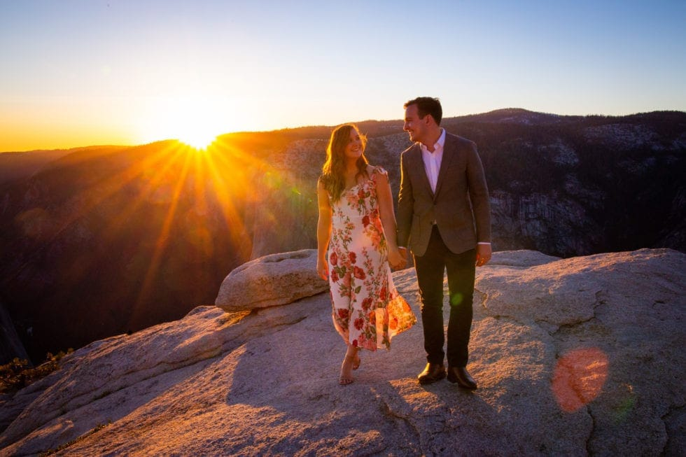 couple walking toward the camera with view of yosemite and setting sun in background