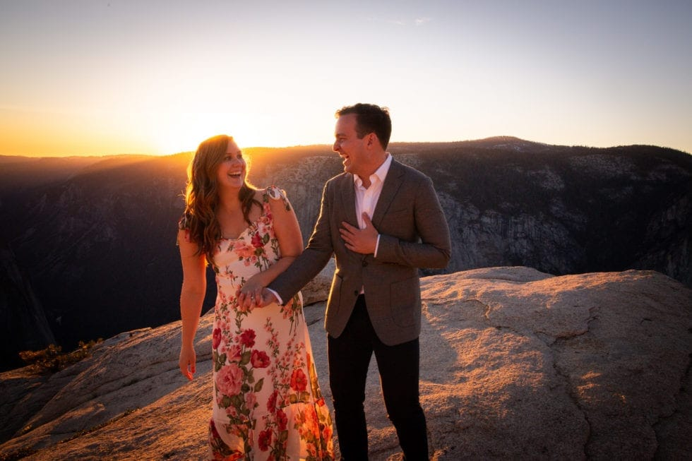 couple holding hands and laughing during yosemite engagement session