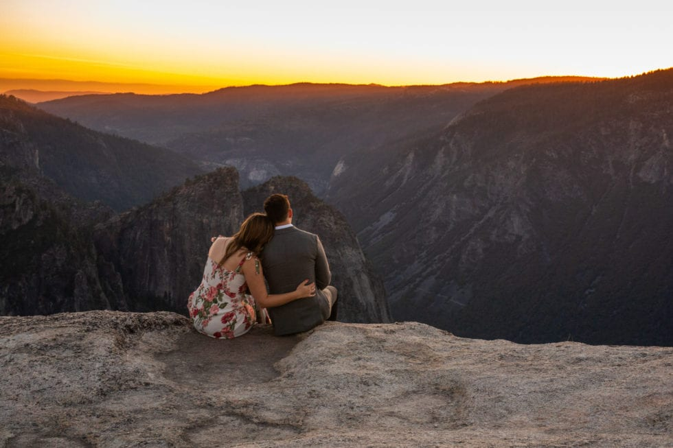 couple sitting on edge and overlooking yosemite during engagement session