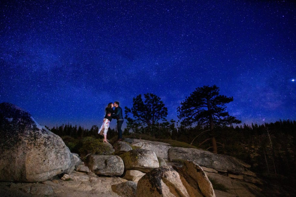 couple kissing with the starry night sky in background