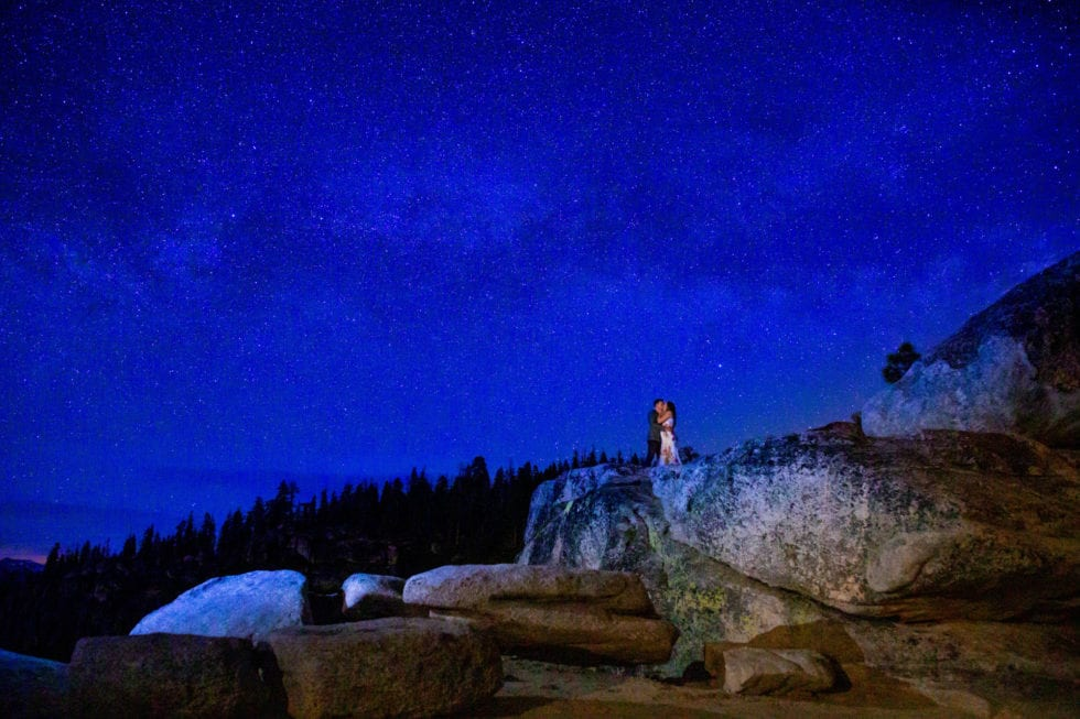 couple embracing with starry night sky behind them during yosemite engagement session