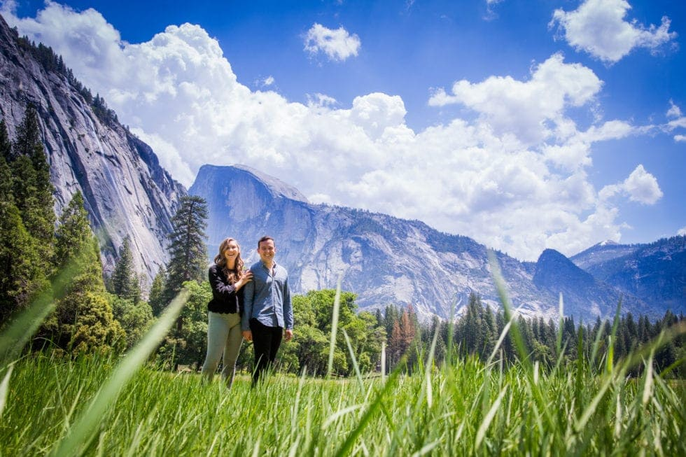 couple holding hands in meadow with half dome in background