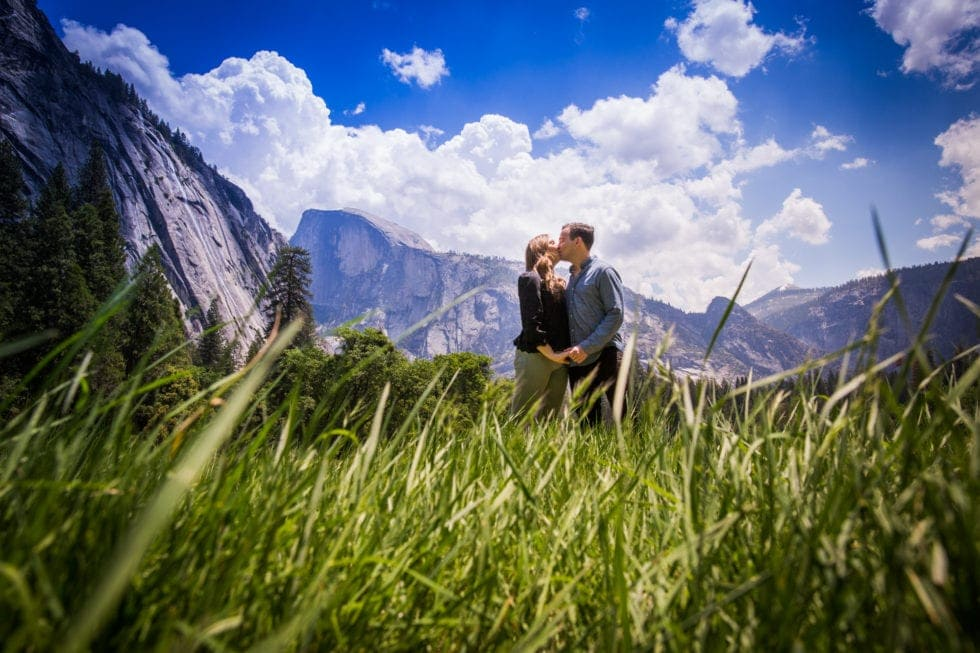 couple holding hands and kissing in meadow in yosemite