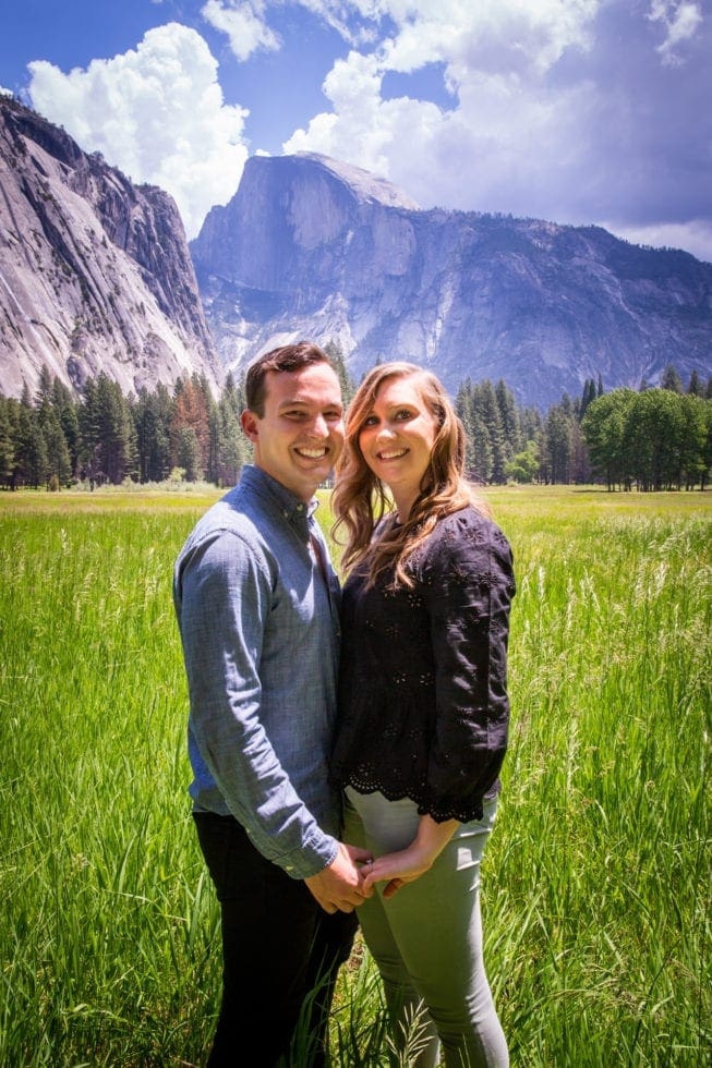 couple holding hands and smiling with half dome in background