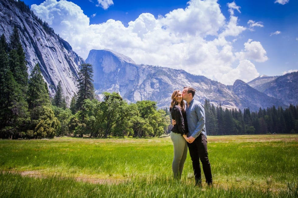 boy kissing his fiances face and holding her hand in front of half dome