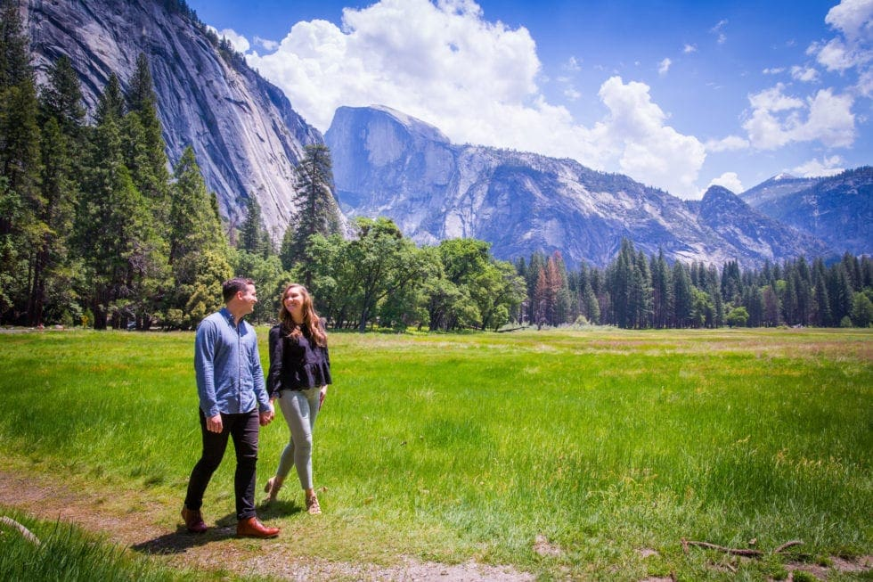 couple holding hands and walking through meadow during yosemite engagement session