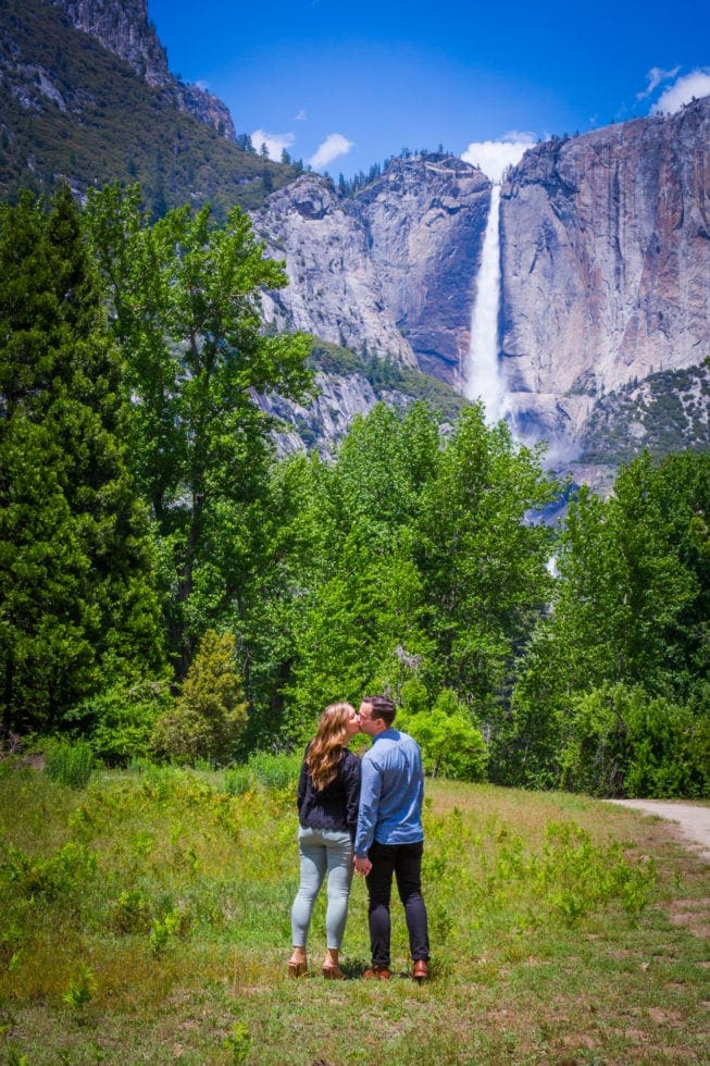 couple holding hands and kissing in front of yosemite falls during yosemite engagement session