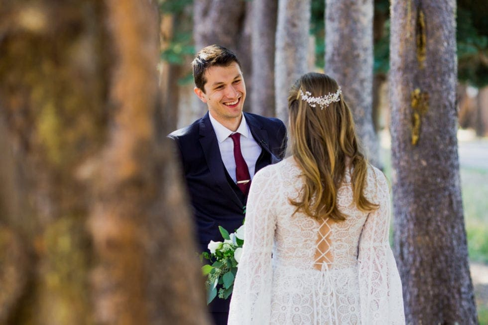 bride and groom smiling at each other during first look in bear valley