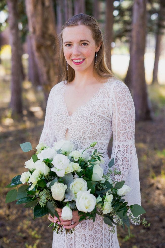 bride holding bouquet and smiling at camera