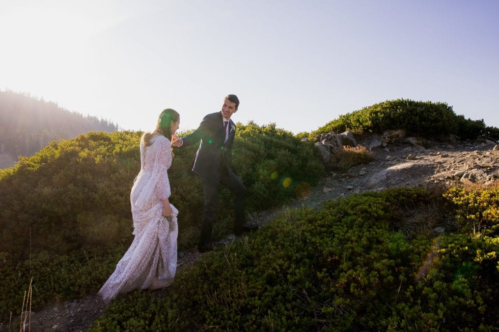 bride and groom holding hands and walking up mountainside in bear valley ca